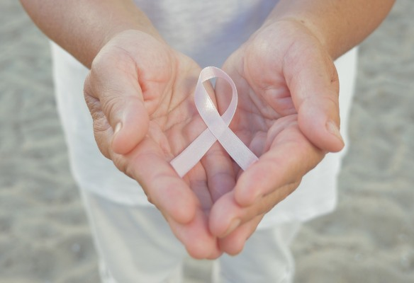 Hands holding pink ribbon